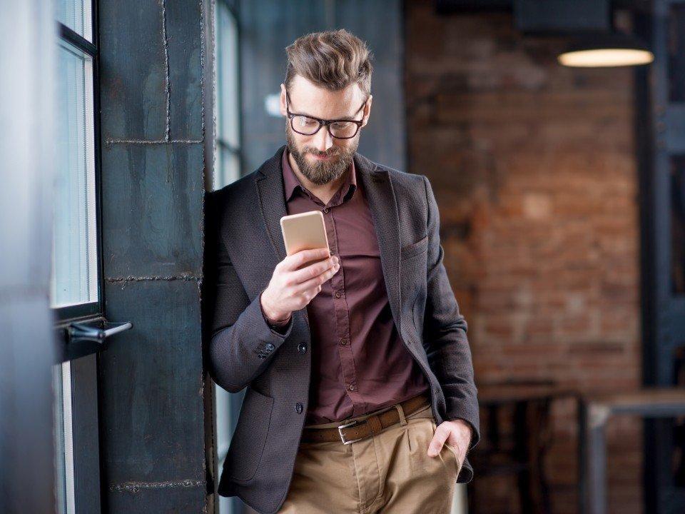 mężczyzna wmarynarce trzymający telefon
